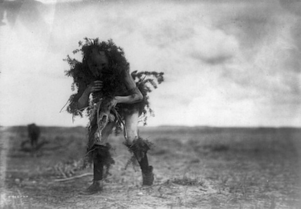 Yebichai, the beggar, Tonenili-Navajo Indian, dressed in spruce branches, 1904-1905.