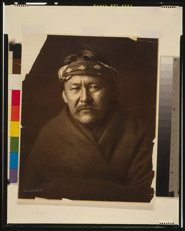 A Navajo man, head-and-shoulders portrait, wearing blanket and headband, facing front, 1904.